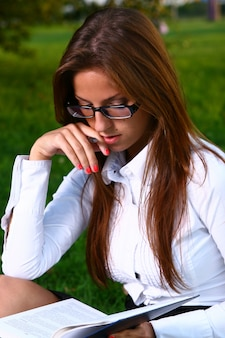 Belle jeune femme étudie dans le parc