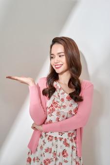 Belle jeune femme eurasienne présentant votre produit très excitant. isolé sur blanc.