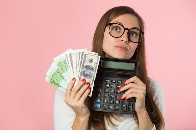 Belle jeune femme avec euro et dollars sur fond rose