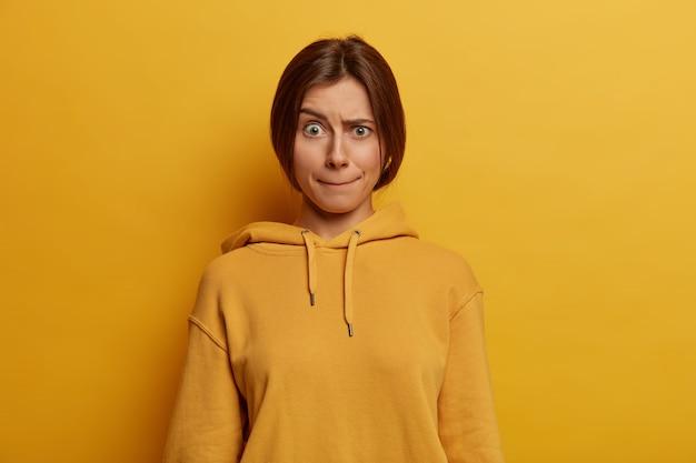 Belle jeune femme européenne aux cheveux noirs appuie sur les lèvres, soulève les sourcils, a une expression de visage inquiète, porte un sweat à capuche décontracté, pose contre un mur jaune, a un regard embarrassé. prise de vue monochrome.