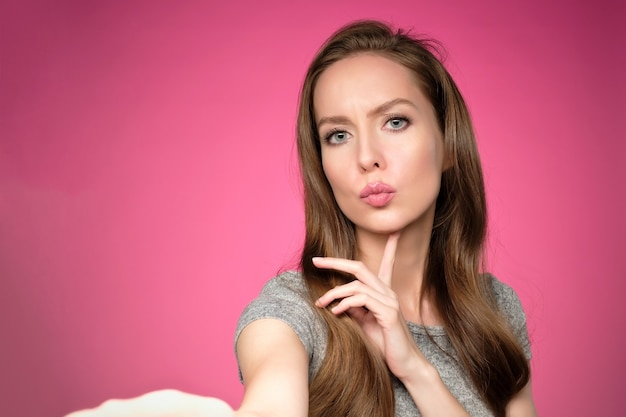Belle jeune femme européenne prenant selfie sur fond rose