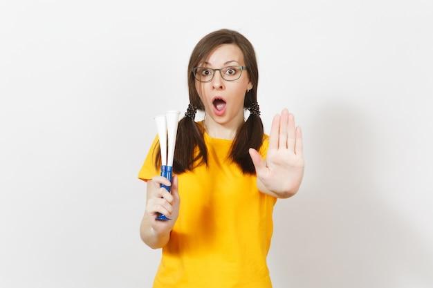 Belle jeune femme européenne avec des queues de cheval amusantes, fan ou joueur à lunettes, geste d'arrêt de spectacle uniforme jaune, tenir le tuyau de football isolé sur fond blanc. fan de sport, concept de mode de vie sain.
