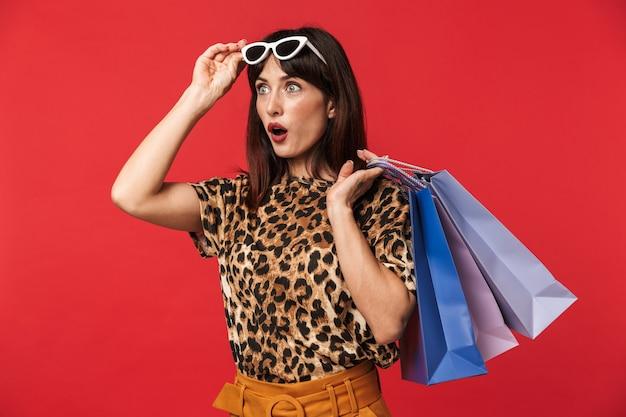 Belle jeune femme excitée vêtue d'une chemise imprimée d'animaux posant isolée sur un mur rouge portant des lunettes de soleil tenant des sacs à provisions.