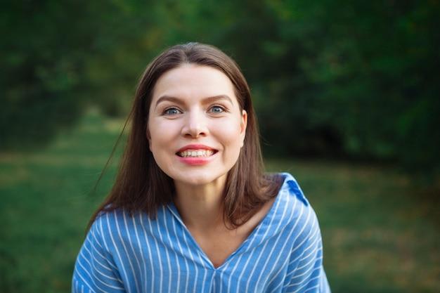 Belle jeune femme à l'extérieur. profiter de la nature. fille souriante en bonne santé dans l'herbe verte. visage jeune belle fille sombre gros plans cheveux courts parc d'été souriant.