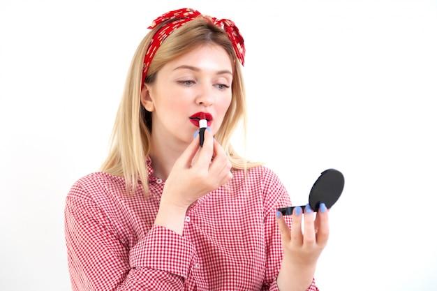 Belle jeune femme faisant du maquillage sur blanc