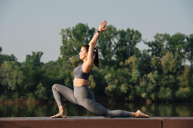 Belle jeune femme faisant du yoga à l'extérieur dans un bel endroit au bord d'une rivière