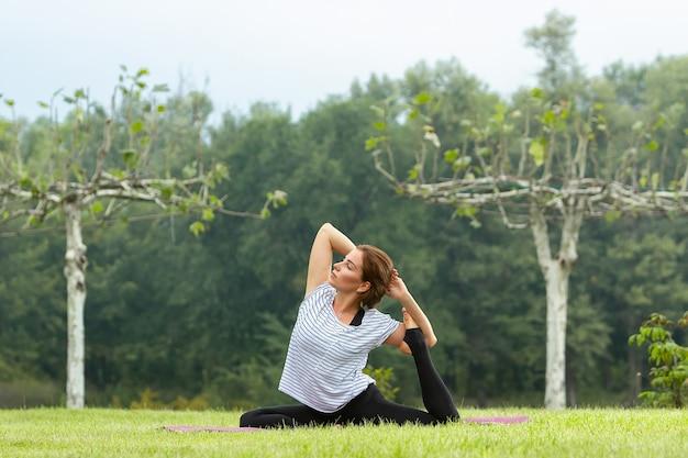 Belle jeune femme faisant des exercices d'yoga dans le parc verdoyant