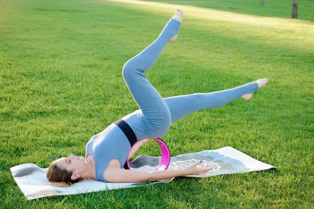 Belle jeune femme faisant des exercices de yoga dans le parc