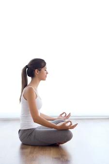 Belle jeune femme faisant des exercices de yoga à la maison.