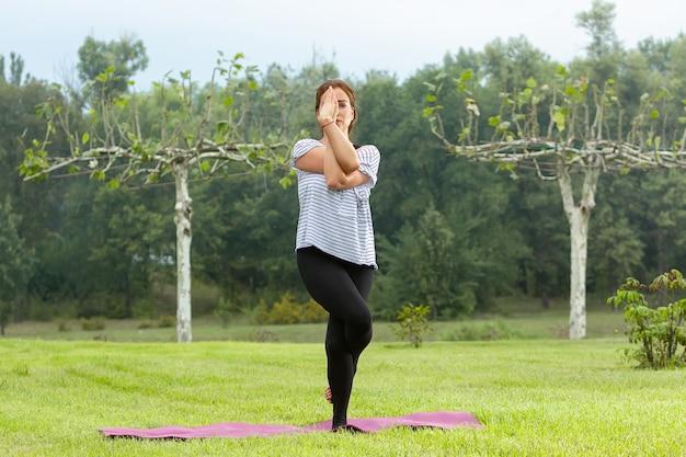 Belle jeune femme faisant des exercices d'yoga en plein air