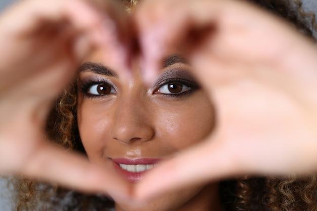 Belle jeune femme faisant en forme de cœur avec les mains