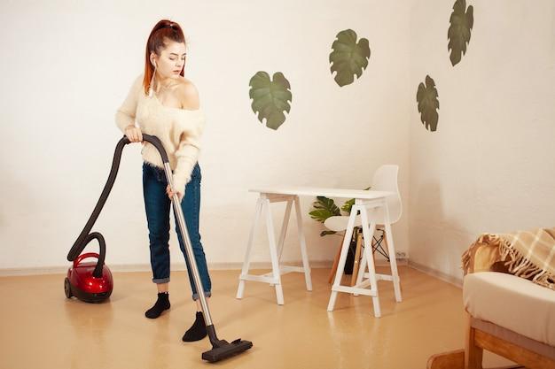 Belle jeune femme faisant le nettoyage dans la maison