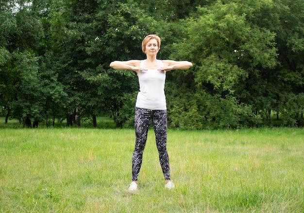 Belle jeune femme fait du sport dans le parc dans la nature. la femme est engagée dans le fitness en vêtements de sport.