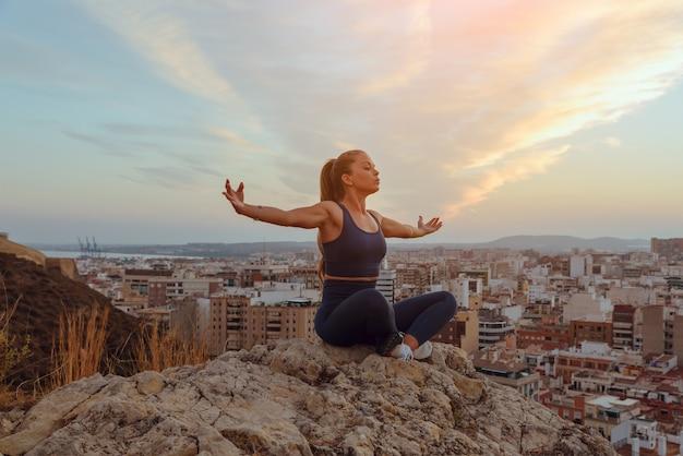 Belle jeune femme fait du yoga à l'extérieur, au sommet d'une crête de montagne dans la ville.