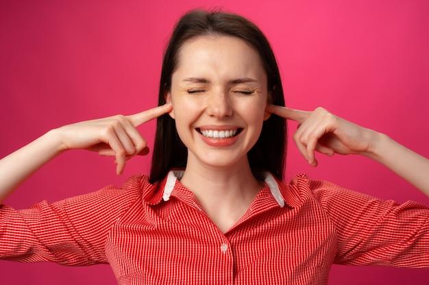 Belle jeune femme fait des gestes qu'elle ne veut pas entendre et tient les mains sur ses oreilles contre le dos rose...
