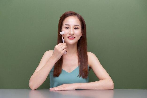 Une belle jeune femme fait un massage facial avec un rouleau de quartz rose. rouleau de massage pour lisser les rides du visage.