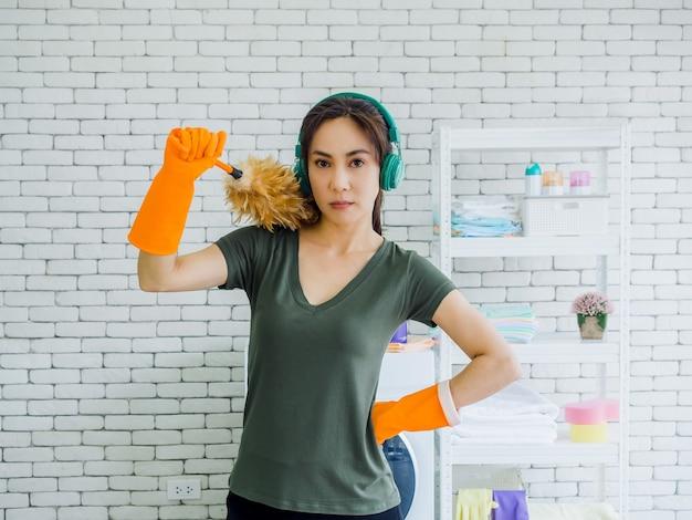 Belle jeune femme, femme au foyer portant des gants en caoutchouc orange, écoutant de la musique avec un casque vert et tenant un plumeau avec un visage fort sur un mur de briques blanches à la maison.