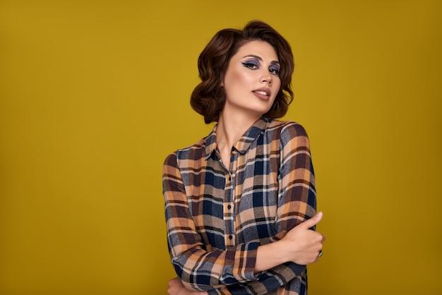 Belle jeune femme, fille rétro bouclée style coiffure posant, debout sur un mur de couleur jaune pastel.