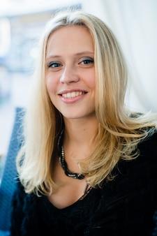 Belle jeune femme fille avec un sourire parfait assis au café en plein air