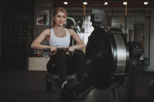 Belle jeune femme de fitness travaillant au gymnase