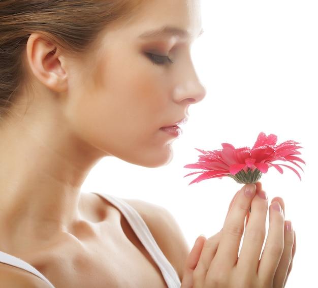 Belle jeune femme avec fleur de gerber isolé sur blanc