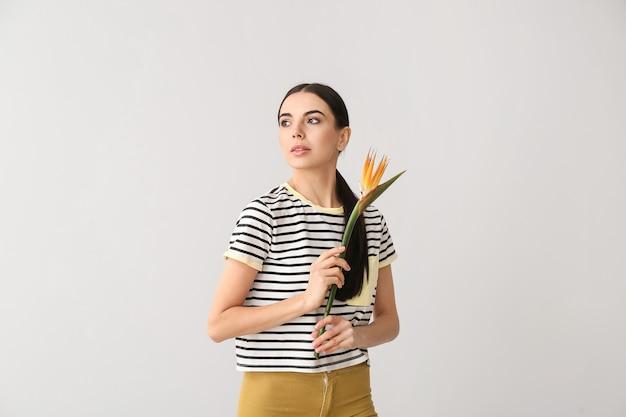 Belle jeune femme avec fleur sur surface grise
