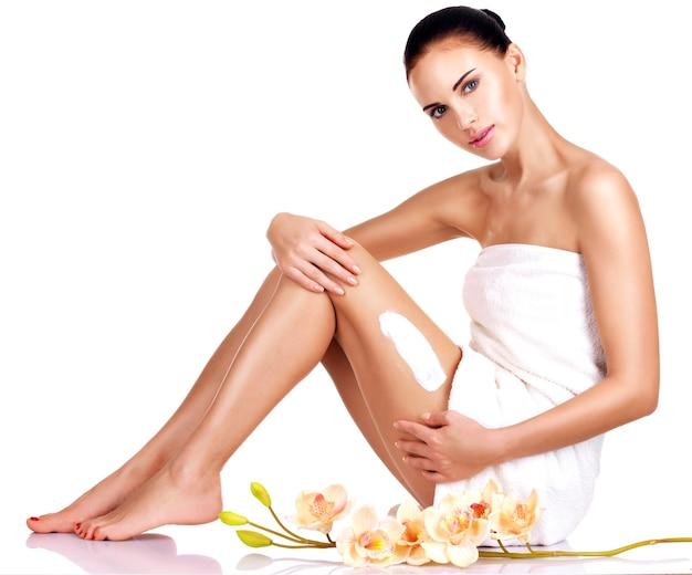 Belle jeune femme avec des fleurs à l'aide de la crème isolé sur blanc