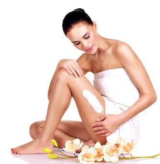 Belle jeune femme avec des fleurs à l'aide de la crème.