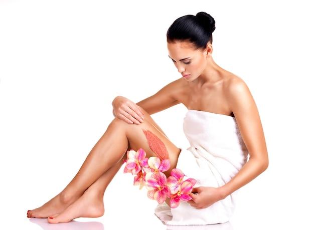 Belle jeune femme avec des fleurs à l'aide d'un gommage. isolé sur blanc