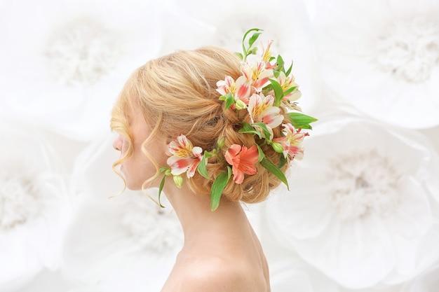 Belle jeune femme avec des fleurs dans les cheveux sur blanc