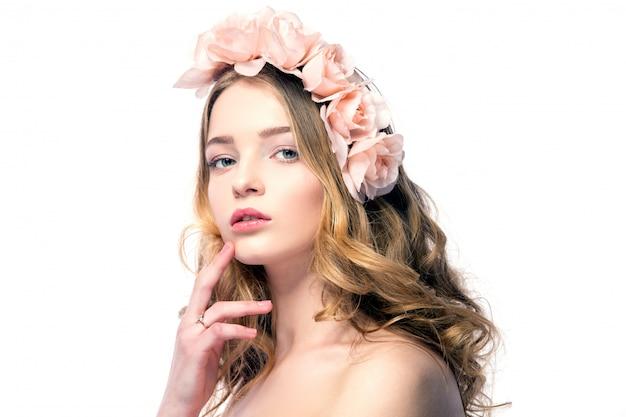 Belle jeune femme avec des fleurs roses sur la tête