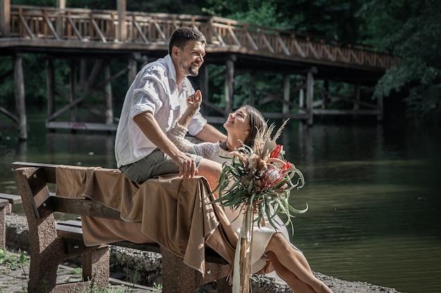 Une belle jeune femme avec des fleurs et son mari sont assis sur un banc et profitent de la communication, d'un rendez-vous dans la nature, de la romance dans le mariage.