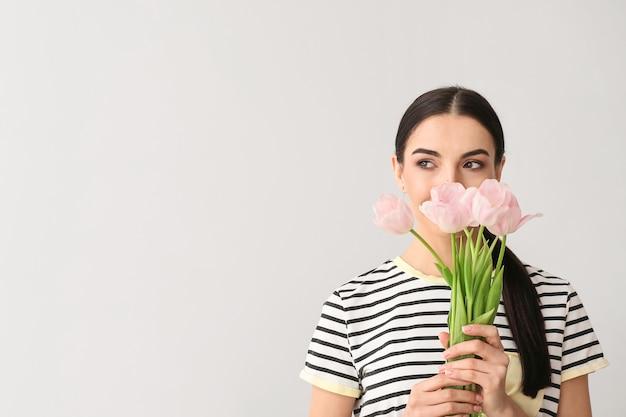 Belle jeune femme avec des fleurs sur une surface grise
