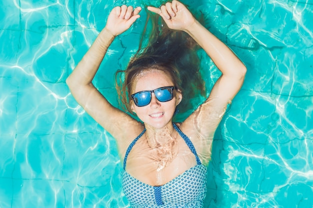Belle jeune femme flottant dans la piscine vue de dessus de détente