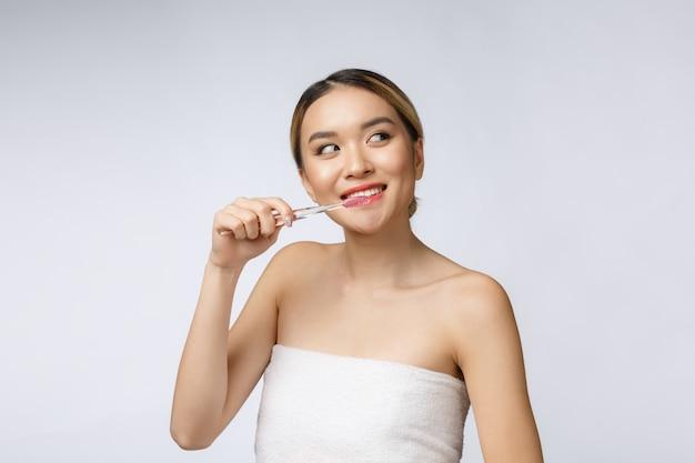 Belle jeune femme sur fond blanc isolé est titulaire d'une brosse à dents, asiatique