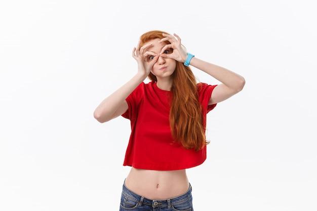 Belle jeune femme sur fond gris visage heureux souriant faisant ok ou signe en verre avec la main sur les yeux en regardant à travers les doigts