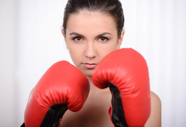 Belle jeune femme en formation à côté d'un sac de boxe.