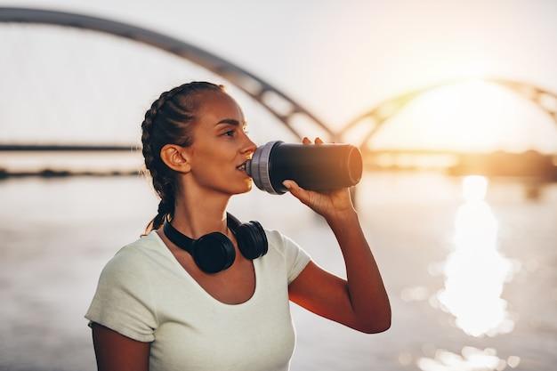Belle jeune femme en forme et en bonne forme qui boit de l'eau à côté de la rivière. beau coucher de soleil en arrière-plan.