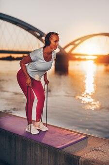 Belle jeune femme en forme et en bonne forme s'exerce seule dans la rue du pont de la ville. elle écoute de la musique avec des écouteurs. beau coucher de soleil en arrière-plan.