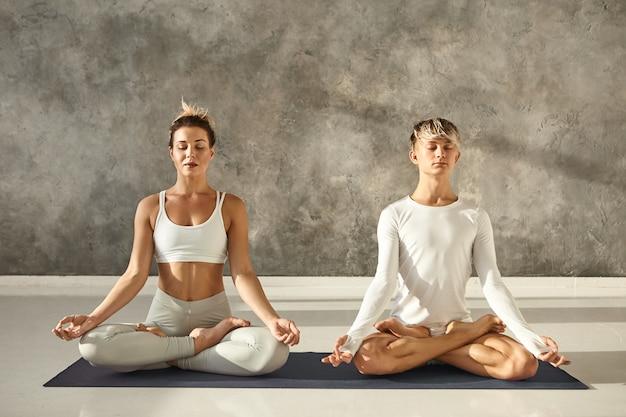Belle jeune femme en forme et homme musclé pratiquant la méditation ensemble en posture de lotus, assis sur un tapis au gymnase avec un mur de fond gris, gardant les yeux fermés et se tenant la main dans mudra
