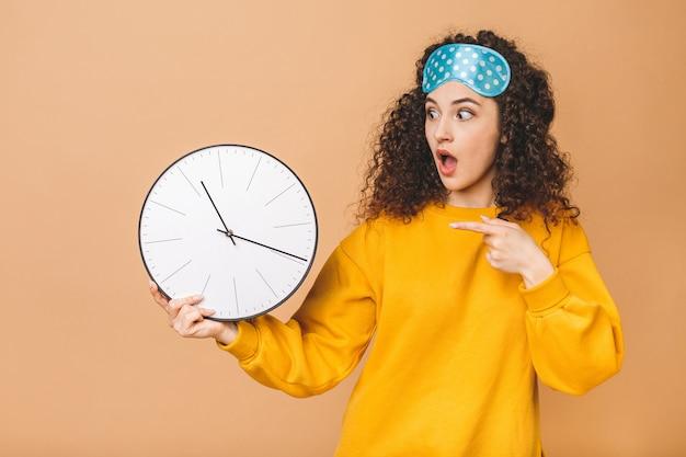 Belle jeune femme frisée étonnée choquée posant sur fond beige avec horloge et masque de sommeil.