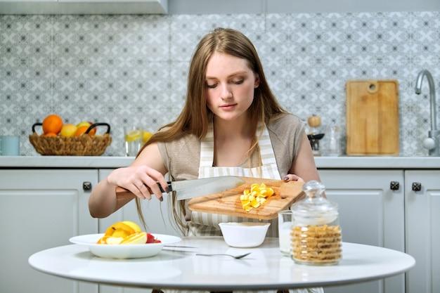 Belle jeune femme avec des fruits dans la cuisine, fille assise à table et coupe l'orange. blogueuse culinaire cuisine salade de fruits à la caméra