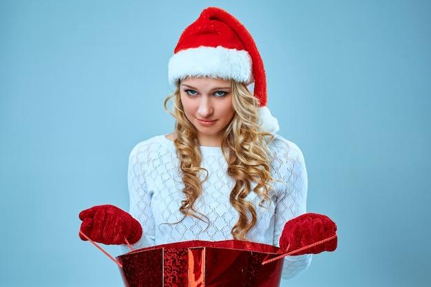 Belle jeune femme frustrée et ennuyée en chapeau de père noël avec un cadeau sur fond bleu