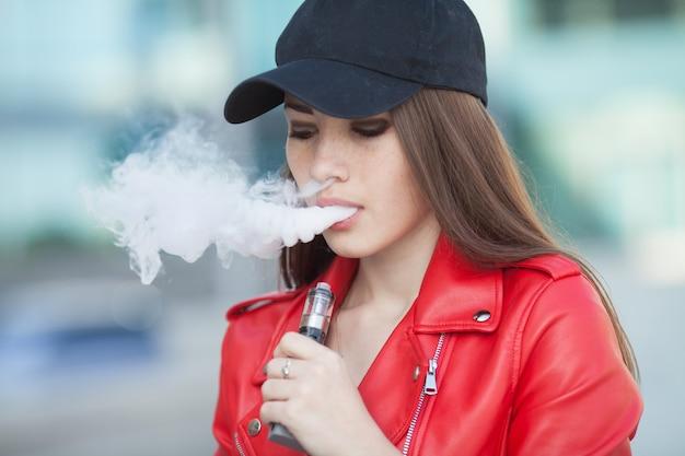 Belle jeune femme fumant (vaping) e-cigarette avec de la fumée