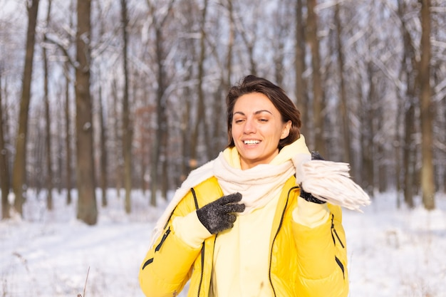Belle jeune femme gaie dans une forêt d'hiver paysage enneigé s'amusant se réjouit en hiver et la neige dans des vêtements chauds