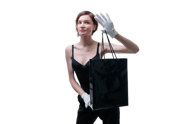Belle jeune femme en gants blancs tient un sac d'artisanat noir dans sa main