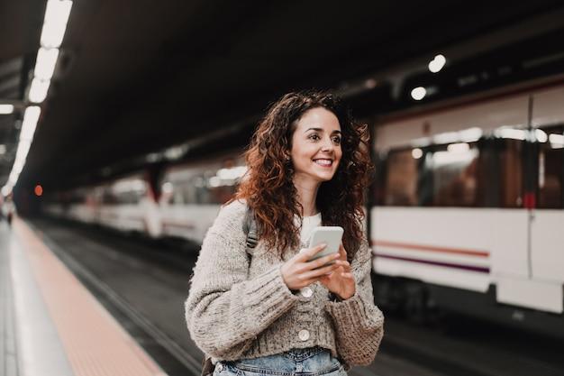 Belle jeune femme à la gare à l'aide d'un téléphone portable avant de prendre un train. vue arrière. voyage, technologie