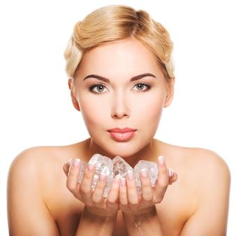 Belle jeune femme avec de la glace dans ses mains. concept de soins de la peau. isolé sur blanc.