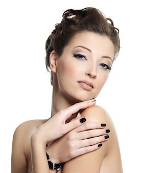Belle jeune femme glamour avec des ongles noirs et une coiffure élégante posant sur blanc