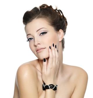 Belle jeune femme glamour avec des ongles noirs et une coiffure élégante posant sur un mur blanc